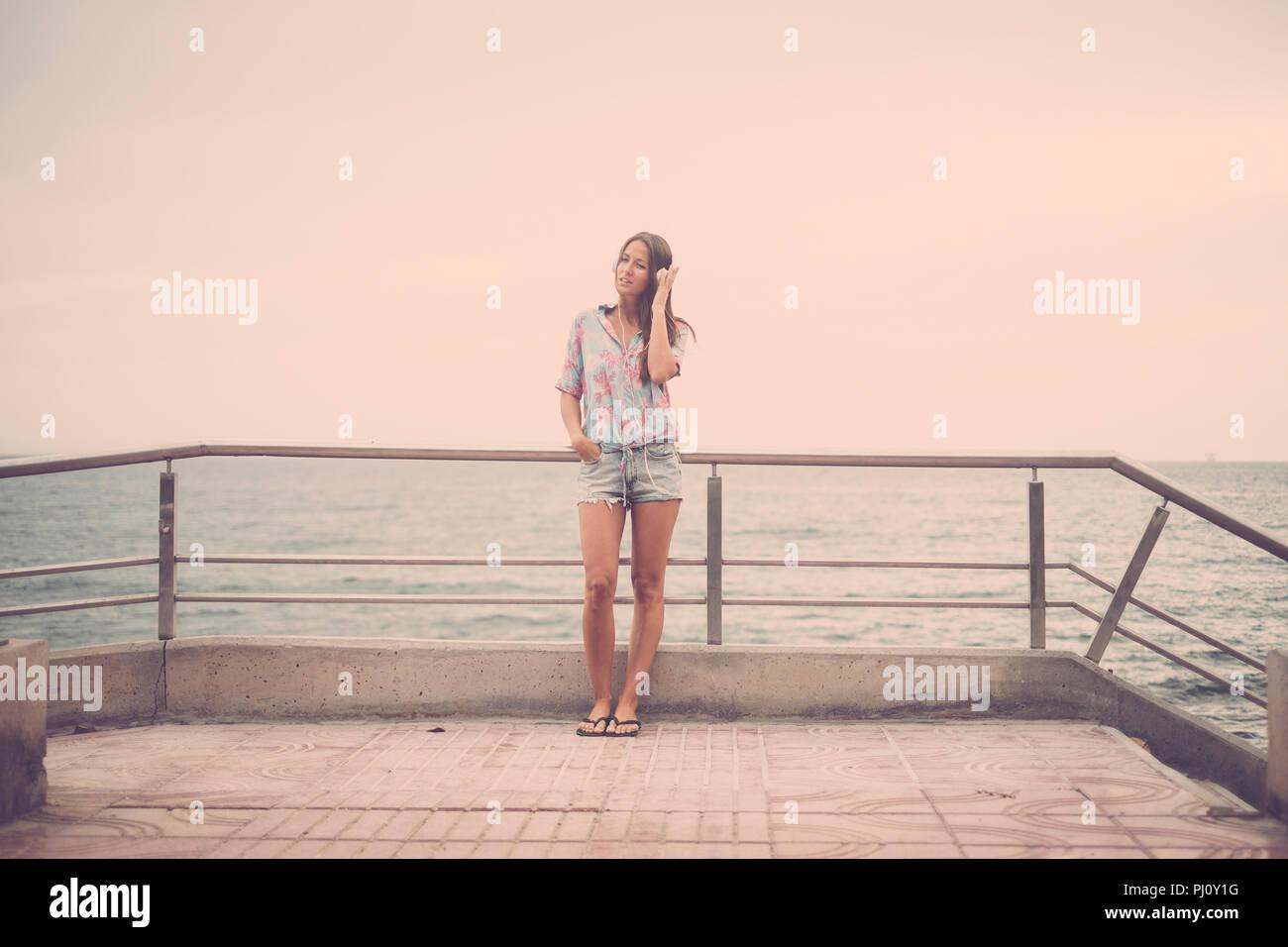 Belle jeune femme caucasian woman standing à la plage sur la route à l'écoute de la musique avec casque et profiter de l'activité de loisirs et de vacances. Photo Stock