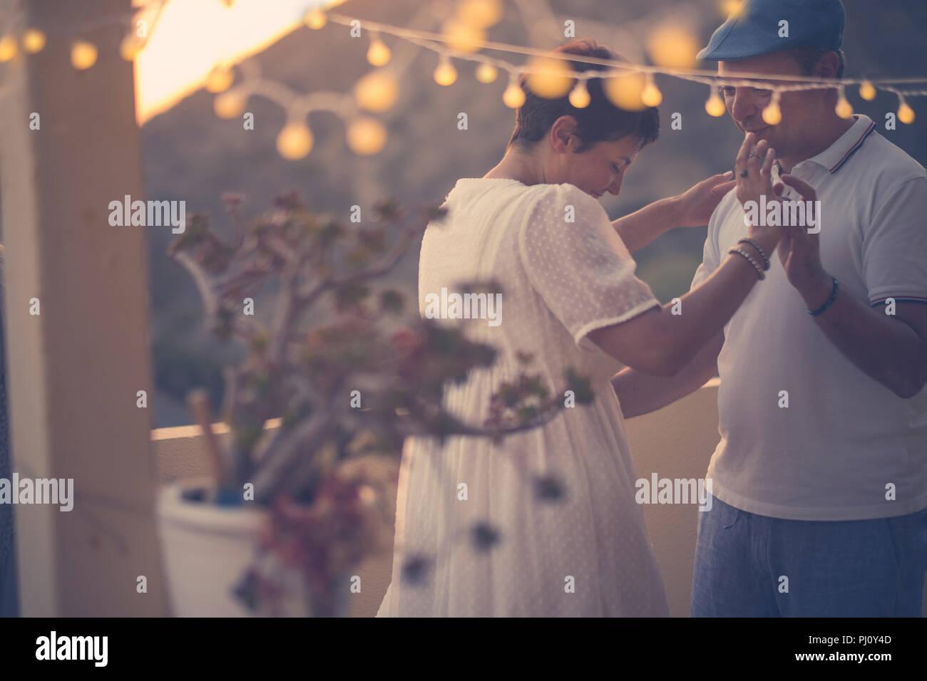 Couple danse romantique avec amour et romance au cours de la vers le bas dans la soirée à la terrasse. Piscine activité de loisirs pour l'âge moyen ne Photo Stock