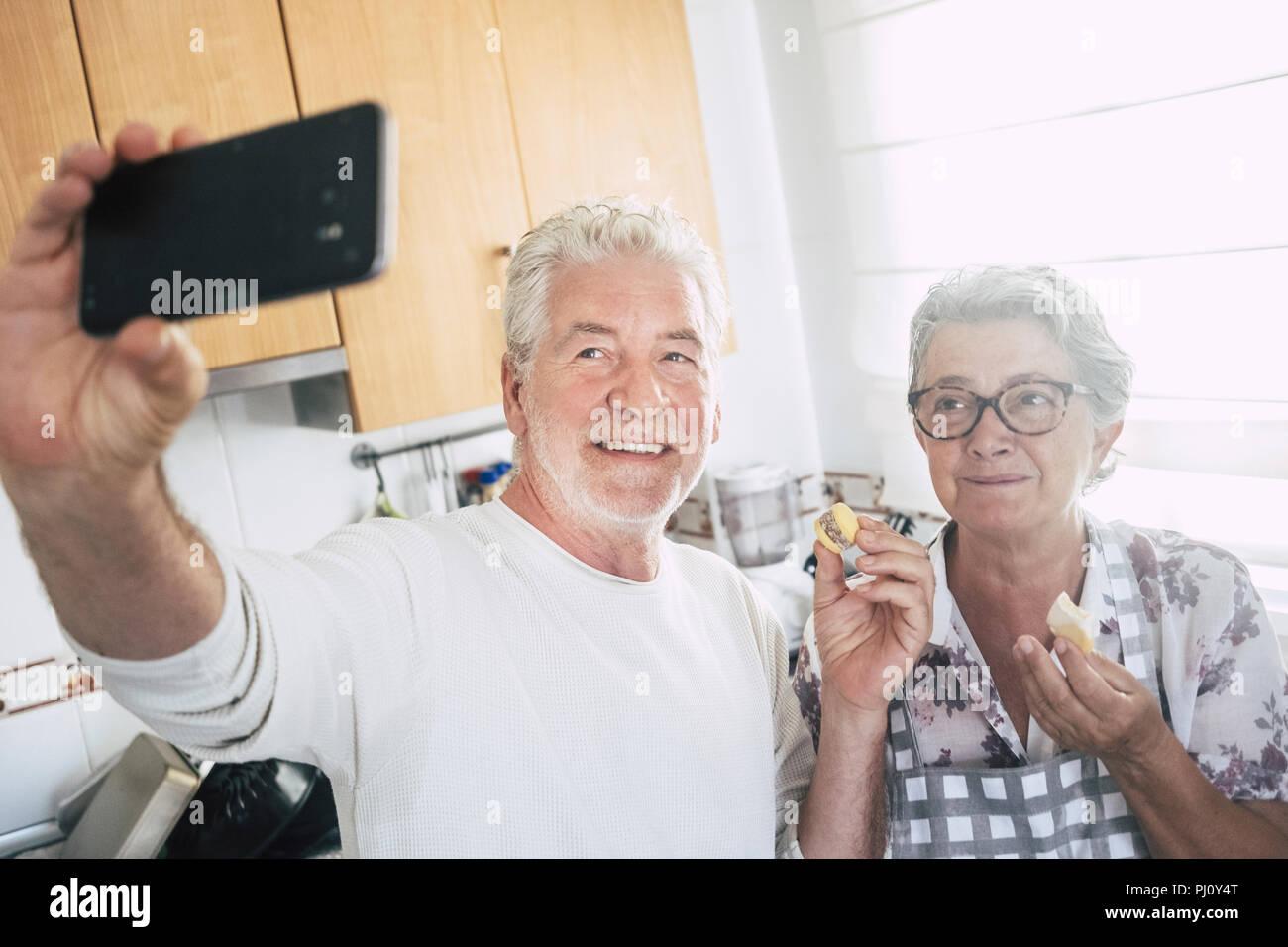 Senior adult caucasian couple heureux à la maison dans la cuisine la cuisine et travailler ensemble avec joie et bonheur. En tenant avec selfies smart phone moderne Photo Stock