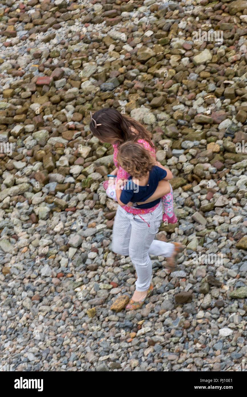 Jeune femme portant un bébé ou un petit enfant marche sur une plage de galets au bord de la mer. Photo Stock