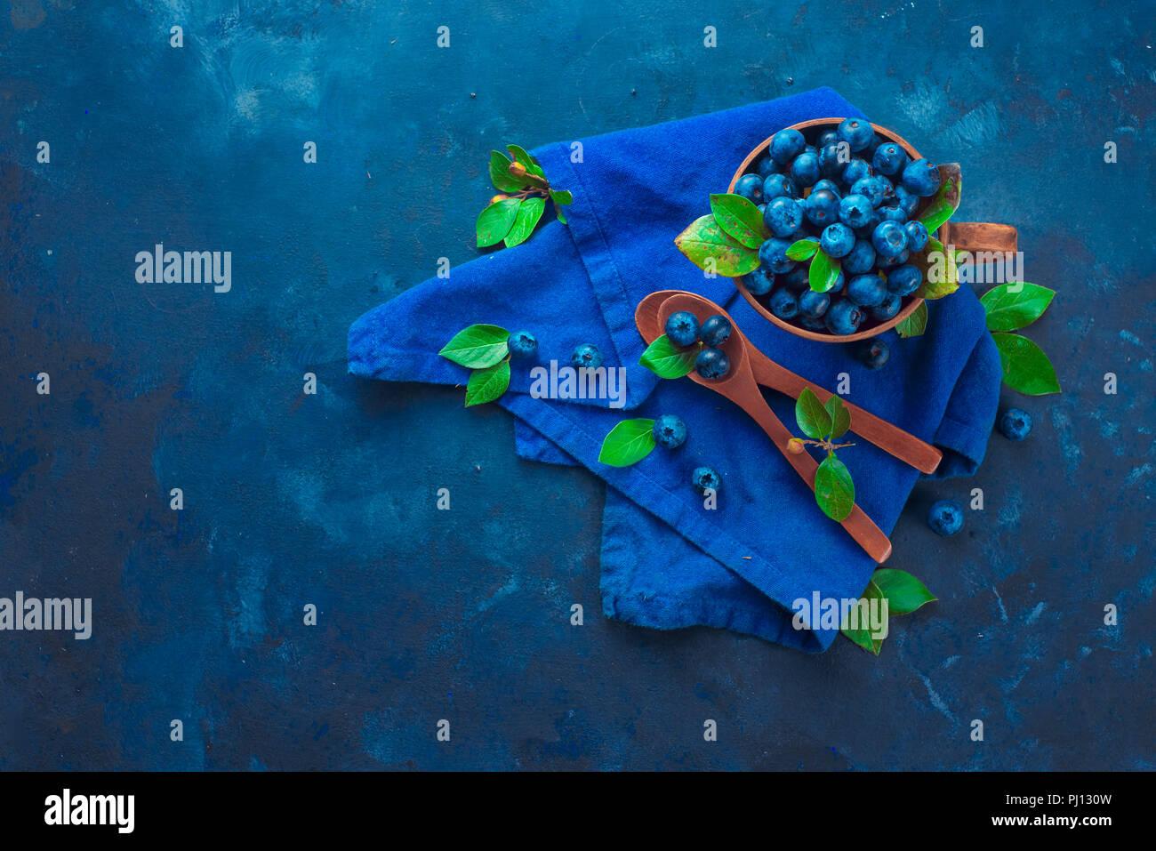 La récolte de petits fruits d'été concept sur un fond bleu foncé avec l'exemplaire de l'espace. Les bleuets dans une tasse en céramique mise à plat. Vue supérieure de la photographie alimentaire Photo Stock
