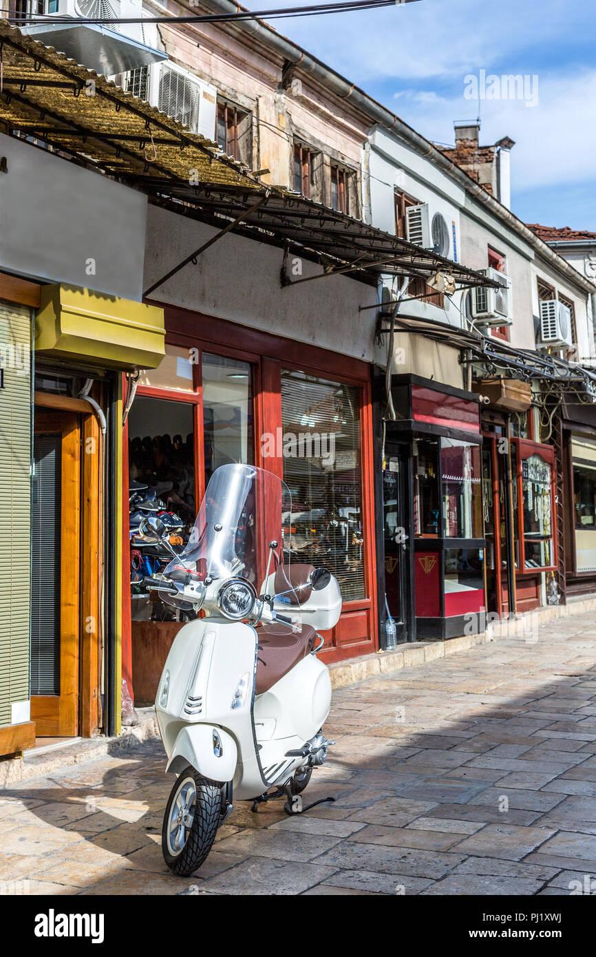 Scooter blanc dans l'ancien style italien classique garée dans la rue Banque D'Images