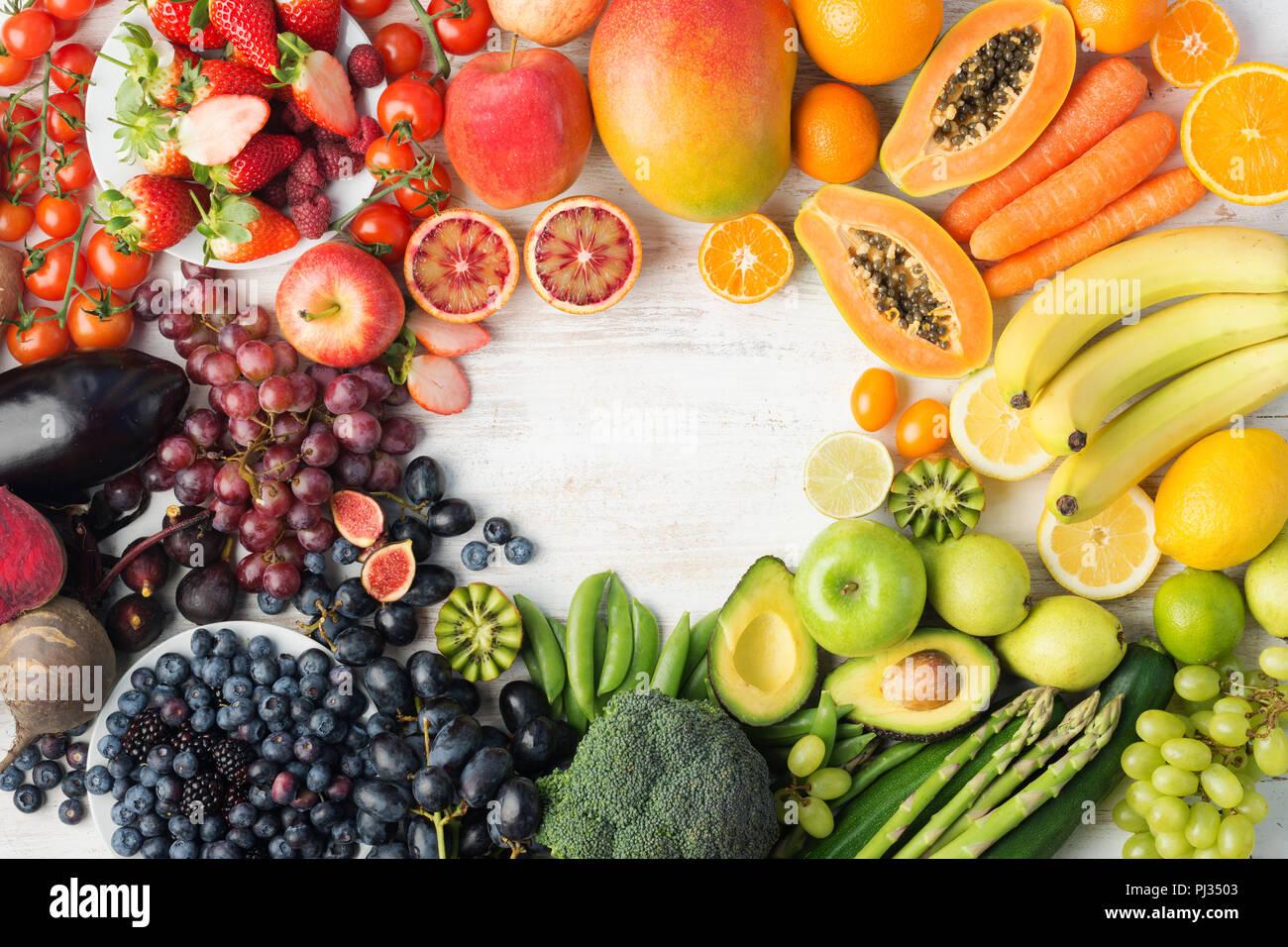 L'alimentation saine, l'varieity des fruits et légumes dans les couleurs arc-en-ciel sur l'off white table dans une trame avec copie espace vertical, vue de dessus, selective focus Photo Stock