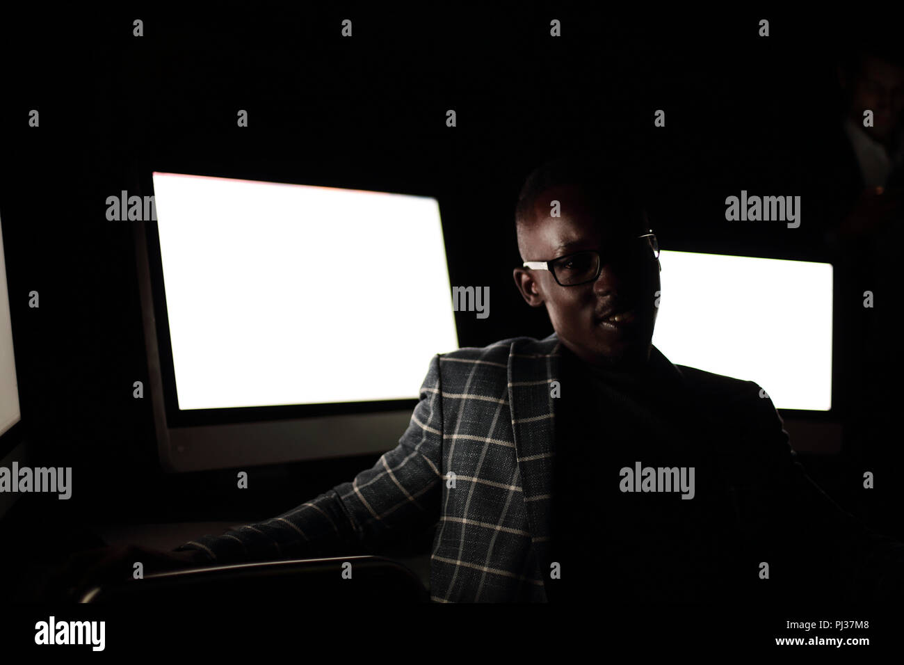 Young businessman sitting in computer room at night Banque D'Images