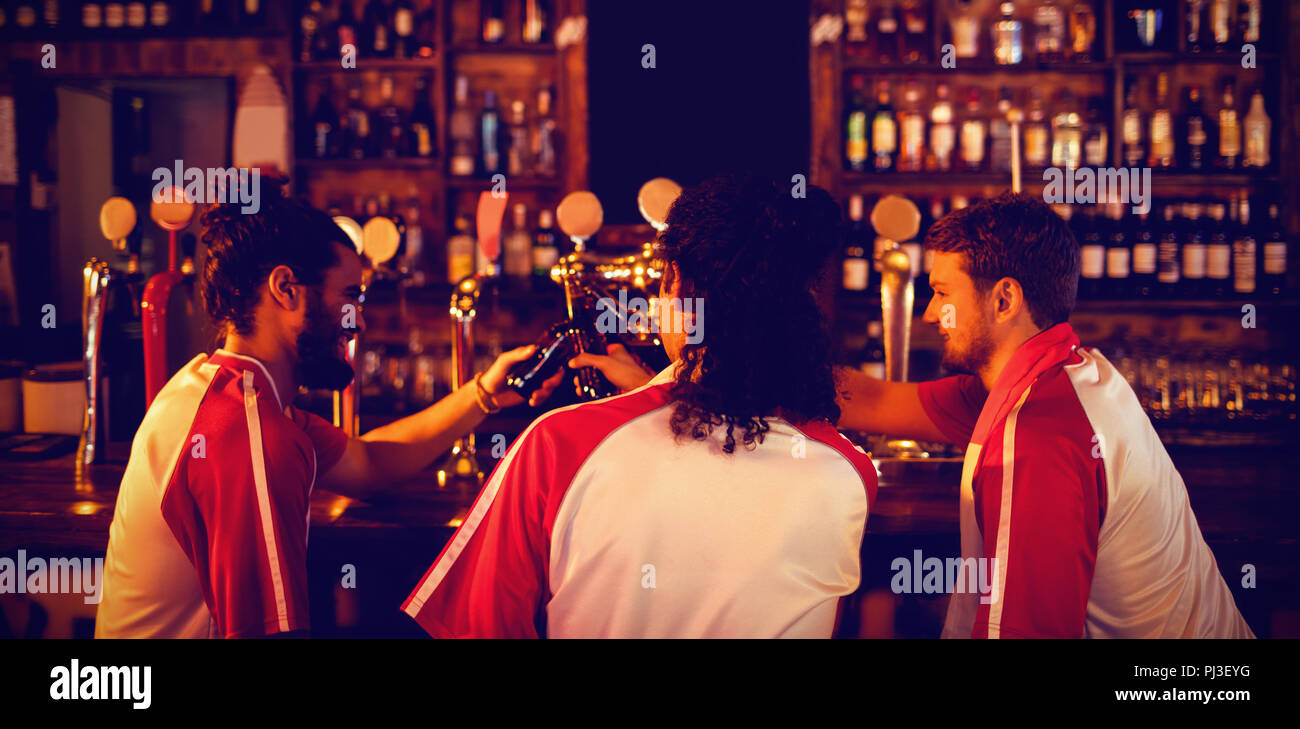 Groupe d'amis masculins toasting beer bottles Photo Stock