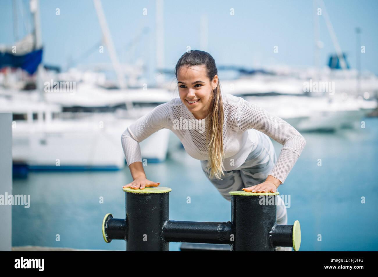 Formation sportive woman outdoors faisant l'exercice par le crossfit ocean pier. Photo Stock