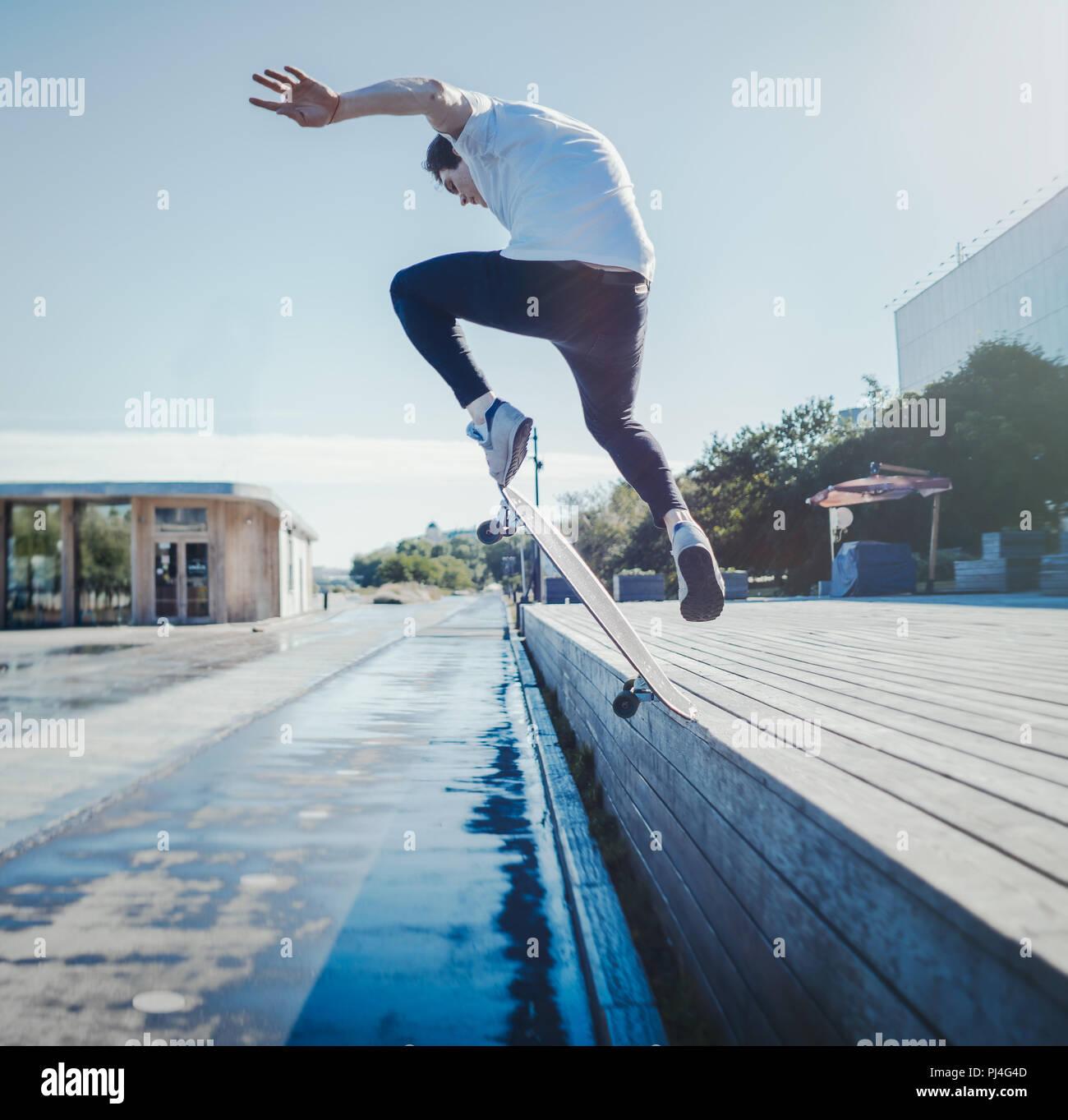 Jeune homme séduisant équitation et sautant longboard dans le parc. Photo Stock