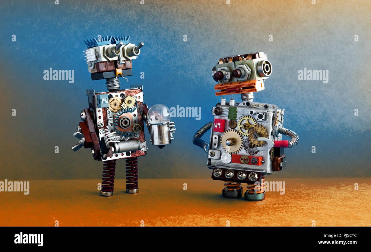 La communication, l'intelligence artificielle des robots concept. Deux personnages robotiques avec ampoule. Photo Stock