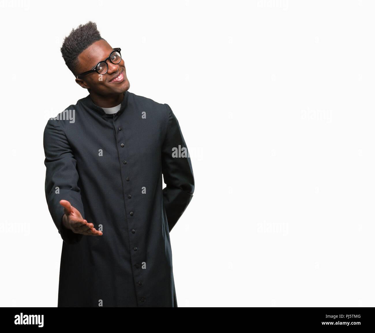 Jeune prêtre américain africain homme sur fond isolé smiling friendly offrant comme message d'handshake et accueillant. Réussite de l'entreprise. Photo Stock