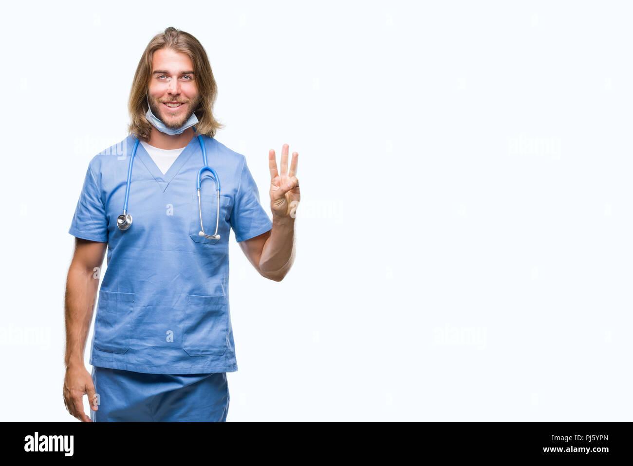Beau jeune homme médecin aux cheveux longs sur fond isolés montrant et pointant vers le haut avec les doigts numéro trois en souriant confiant et heureux. Photo Stock