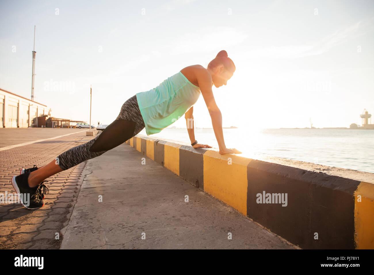 Femme Fitness faire poussez se lève une soirée d'entraînement de formation Concept vue côté sport style de vie sain Photo Stock