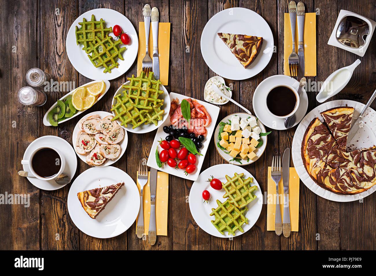 Petit déjeuner d'un tableau. Brunch de fête, ensemble avec divers repas gaufres Épinards, saumon, fromage, olives, roulades de poulet et le gâteau au fromage. Vue d'en haut. Mise à plat Photo Stock