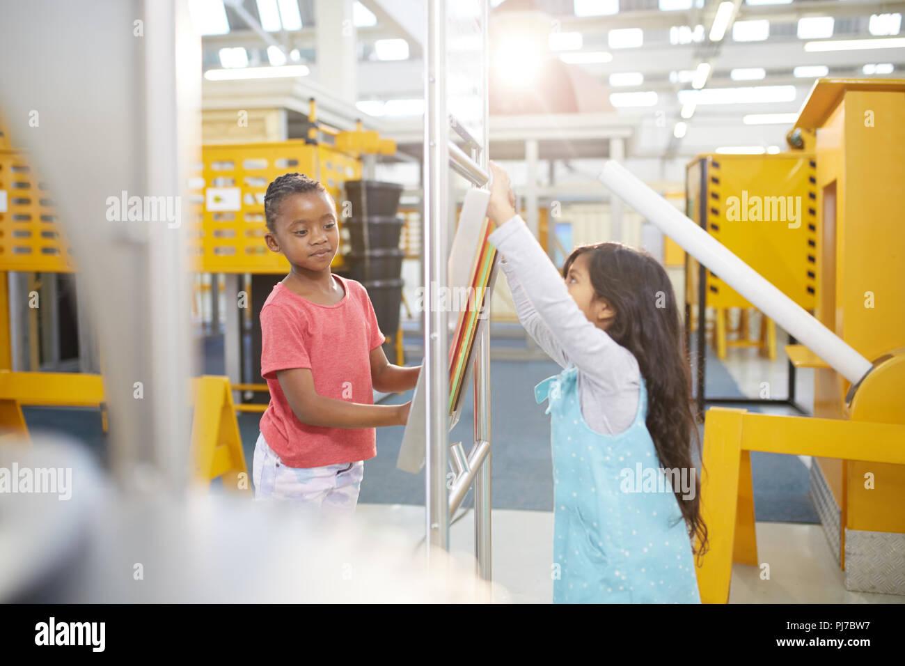 Curieux de jeunes filles, jouant à l'exposition interactive dans science center Photo Stock