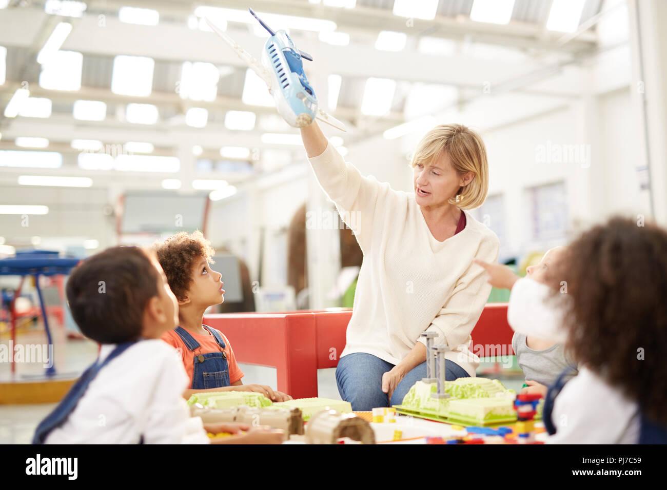 Les enfants curieux professeur regarder avec toy airplane dans science center Photo Stock