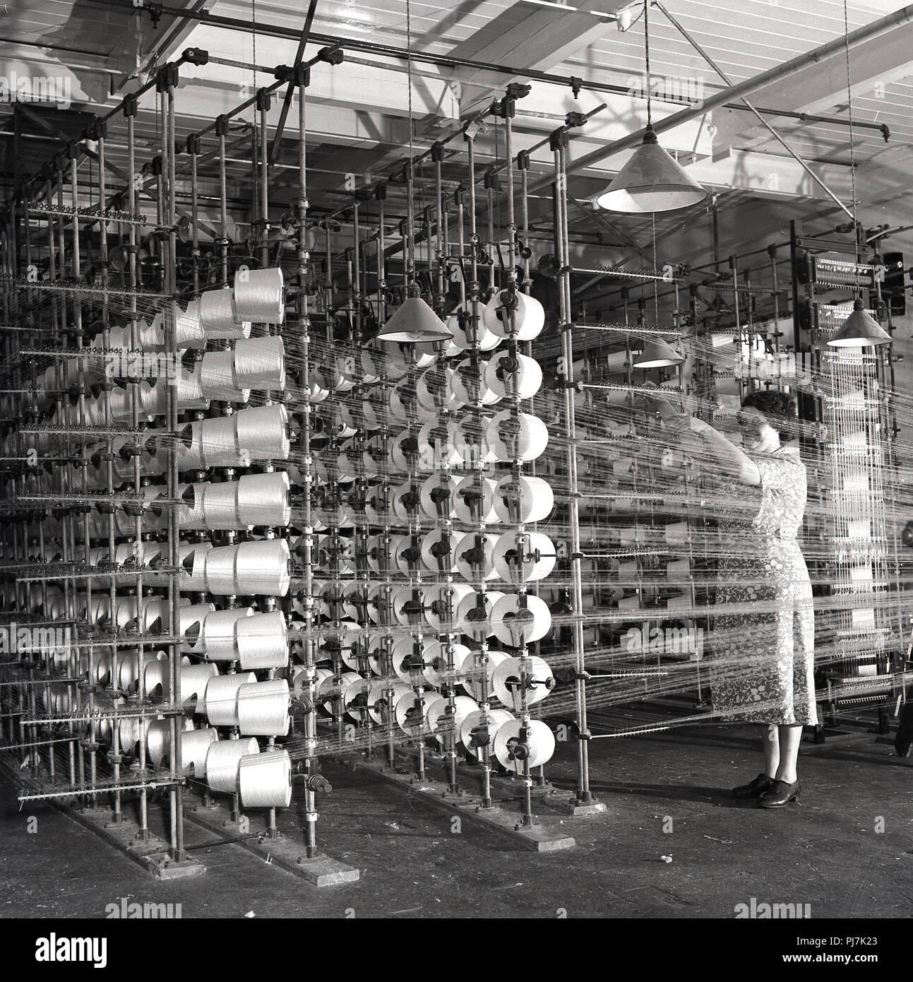 Années 1950, historique, fabrication de textile, une femelle adulte travailleur dans l'aire de contrôle de l'axes ou bobines de fil à l'intérieur d'une usine de textile, l'Irlande du Nord, Royaume-Uni. Banque D'Images