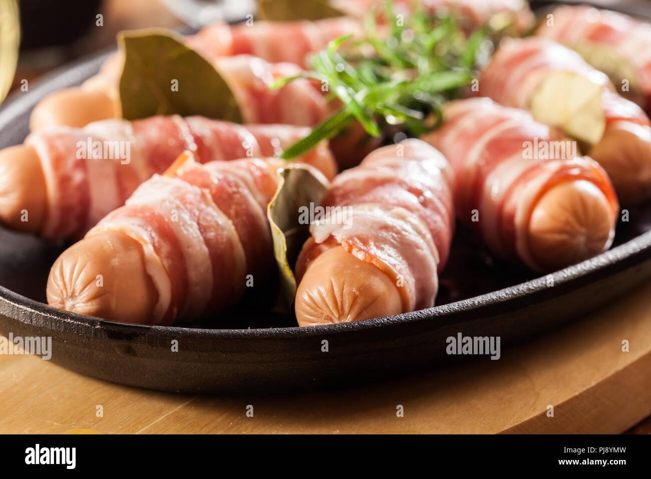 Les porcs dans des couvertures. Mini saucissons crus enveloppés dans du bacon fumé cuit prêt à Banque D'Images