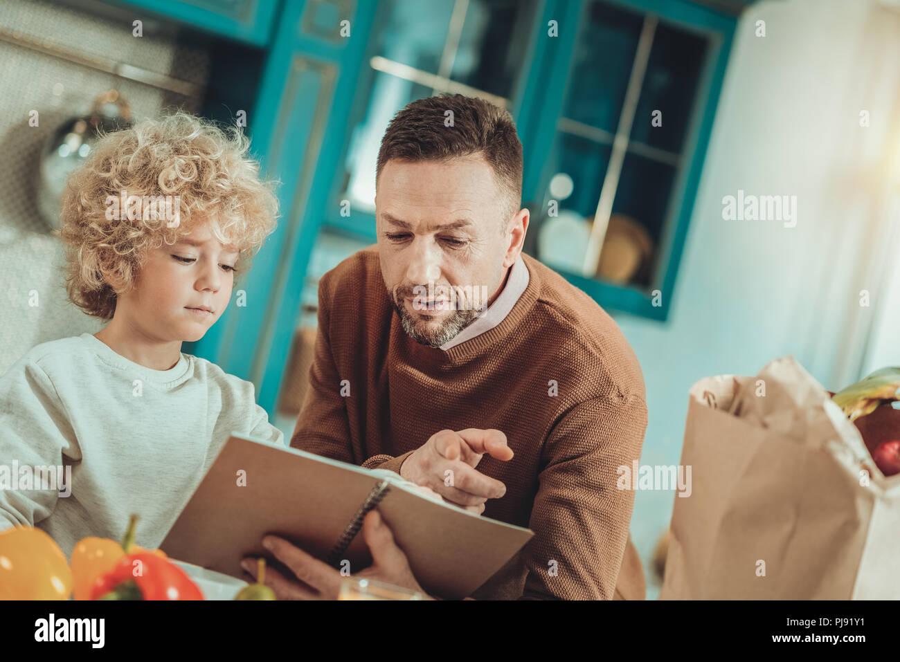 L'homme et l'enfant la lecture d'une fiche Photo Stock