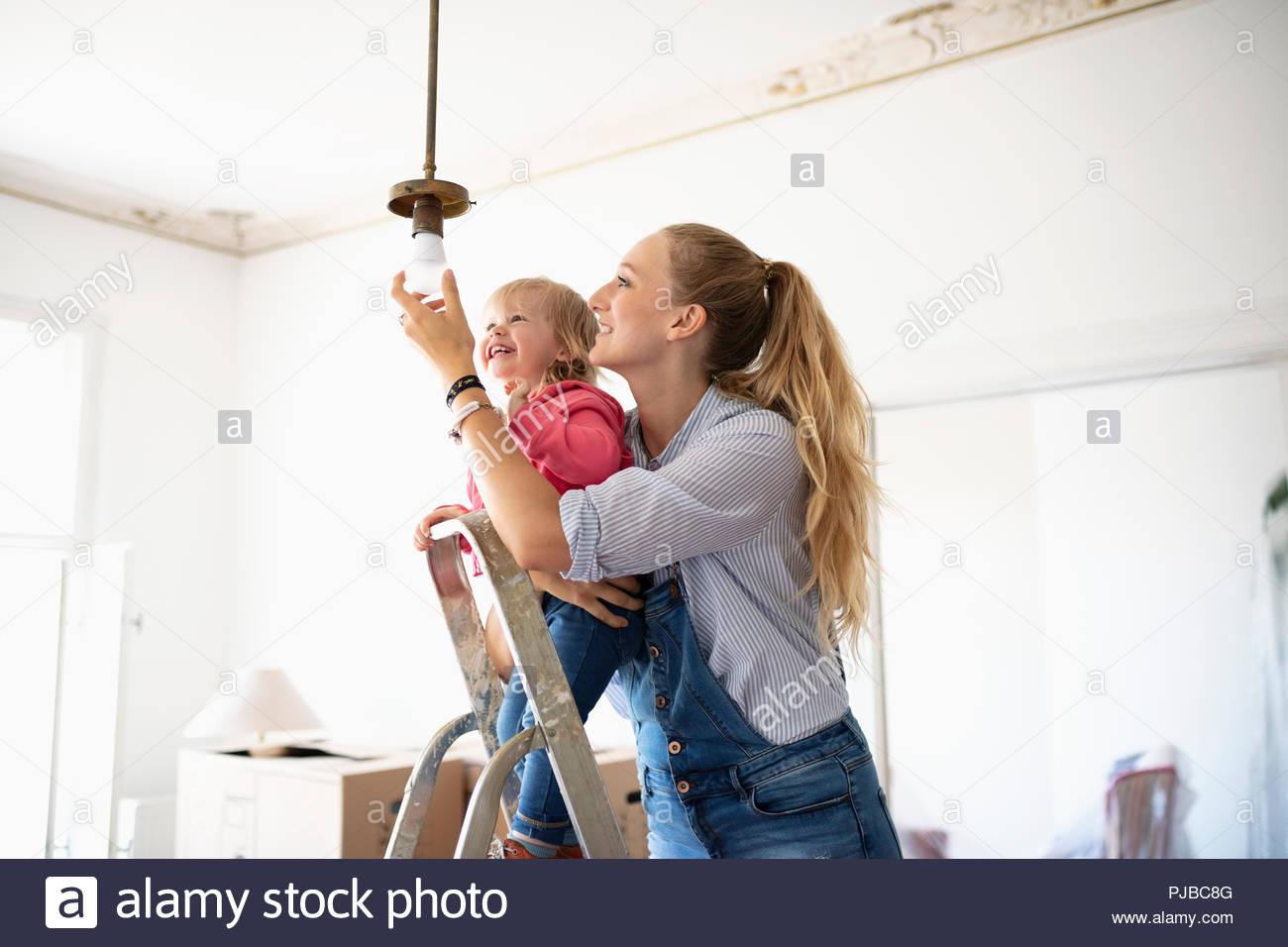 Mère et fille à monter l'évolution des dispositifs de lumière Photo Stock