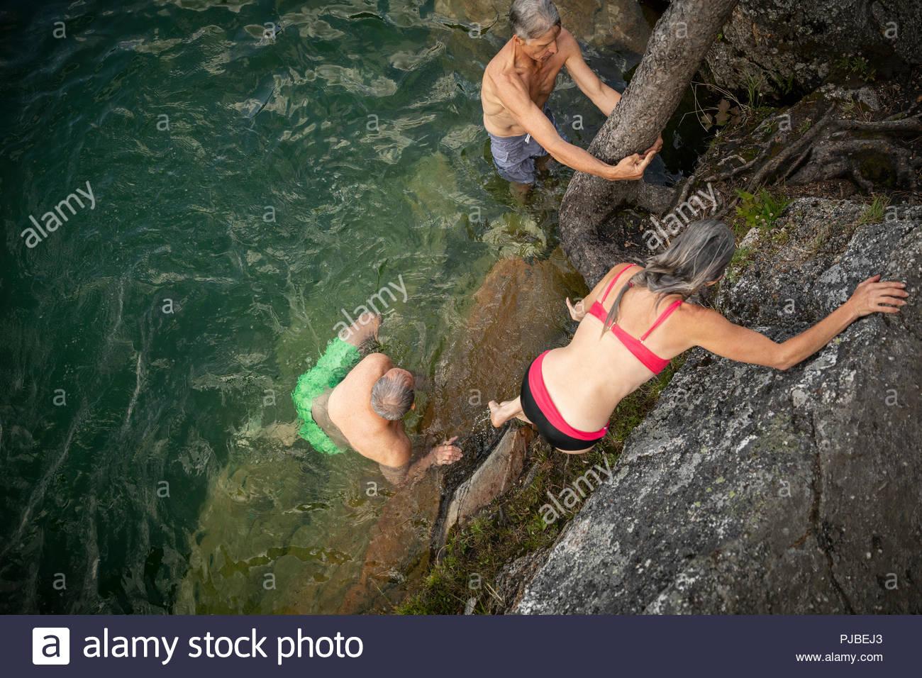Les couples d'âge mûr nager dans le lac, rochers d'escalade Photo Stock