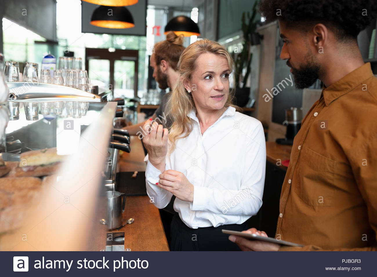 Propriétaire de café barista et parler Photo Stock
