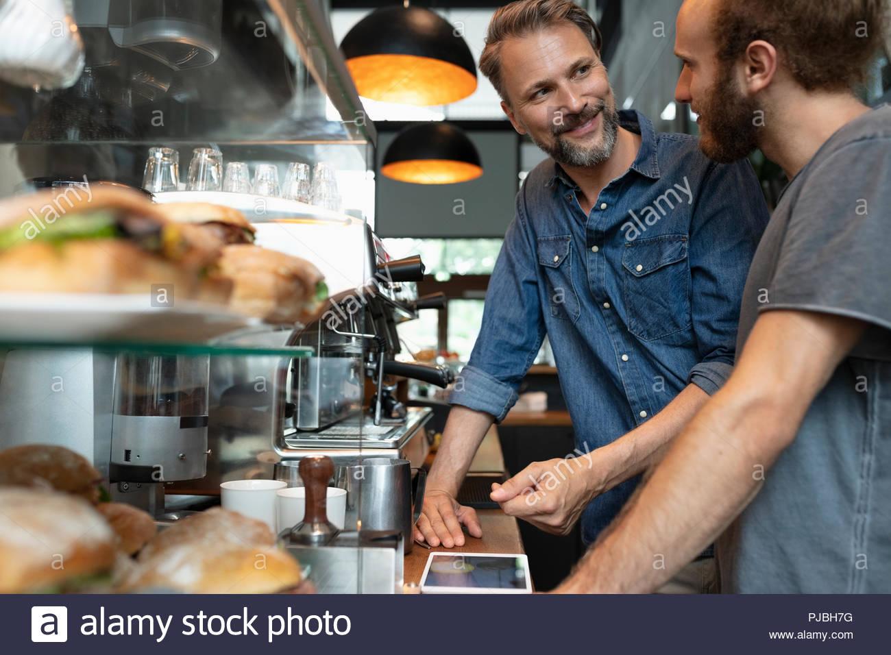 Café mâle propriétaire avec tablette numérique parlant avec barista Photo Stock