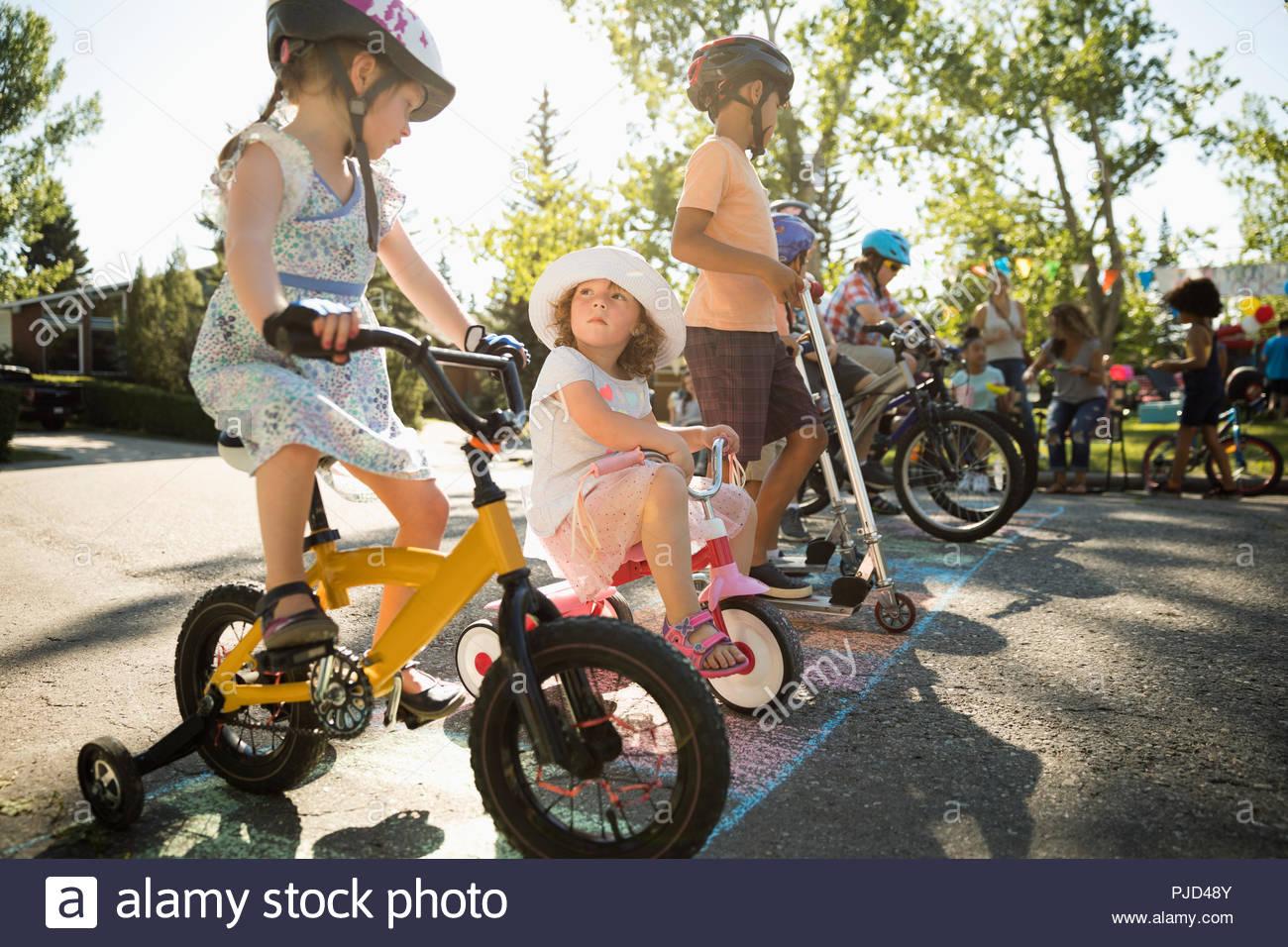 Sur les bicyclettes pour enfants prêt pour la course à la ligne de départ à l'été fête de quartier Photo Stock