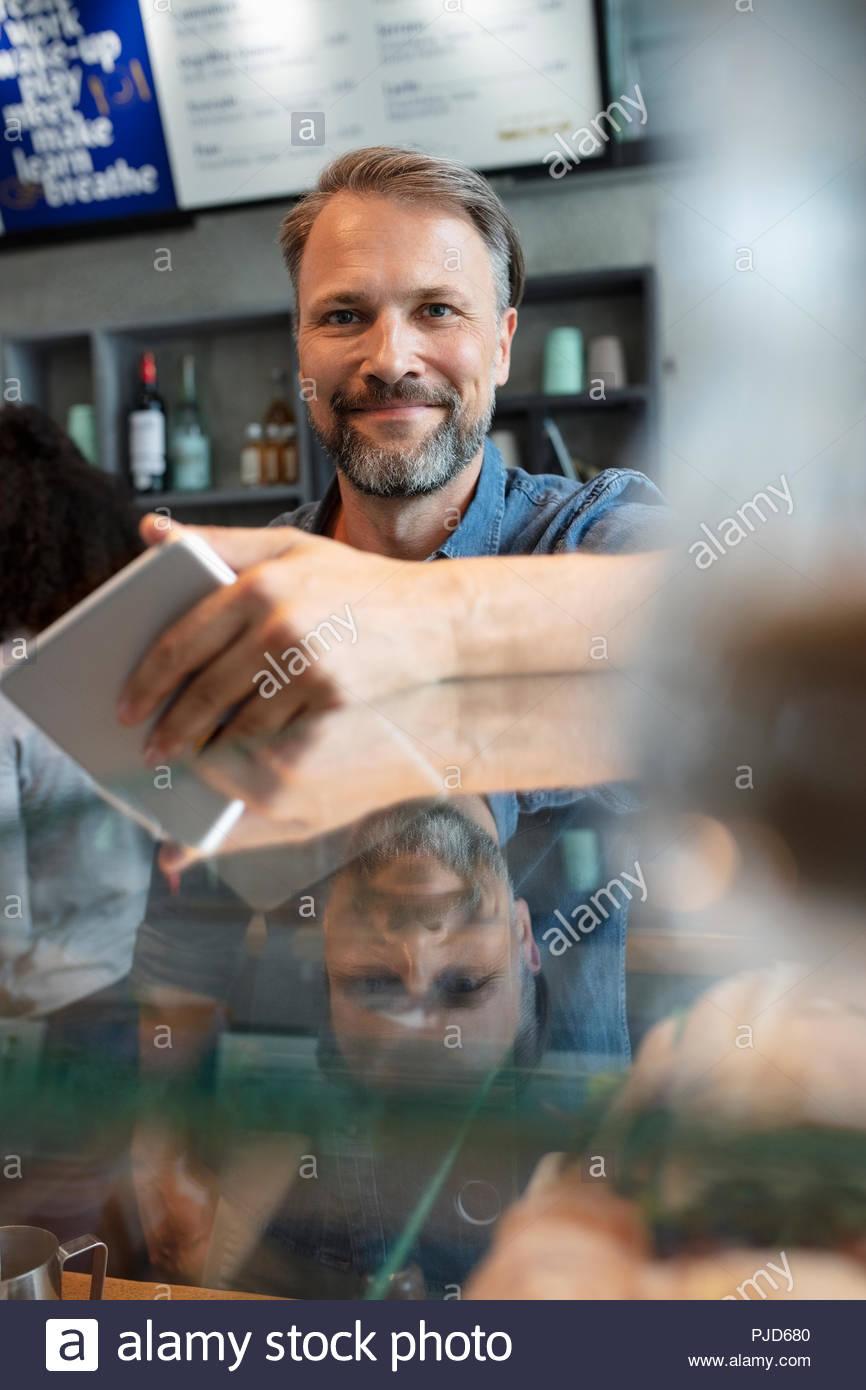 Portrait confiant homme cafe owner with digital tablet Photo Stock