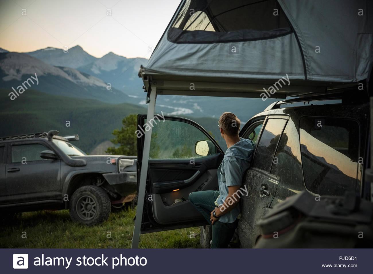 L'homme réfléchi à la montagne à distance sur SUV colline, Alberta, Canada Photo Stock