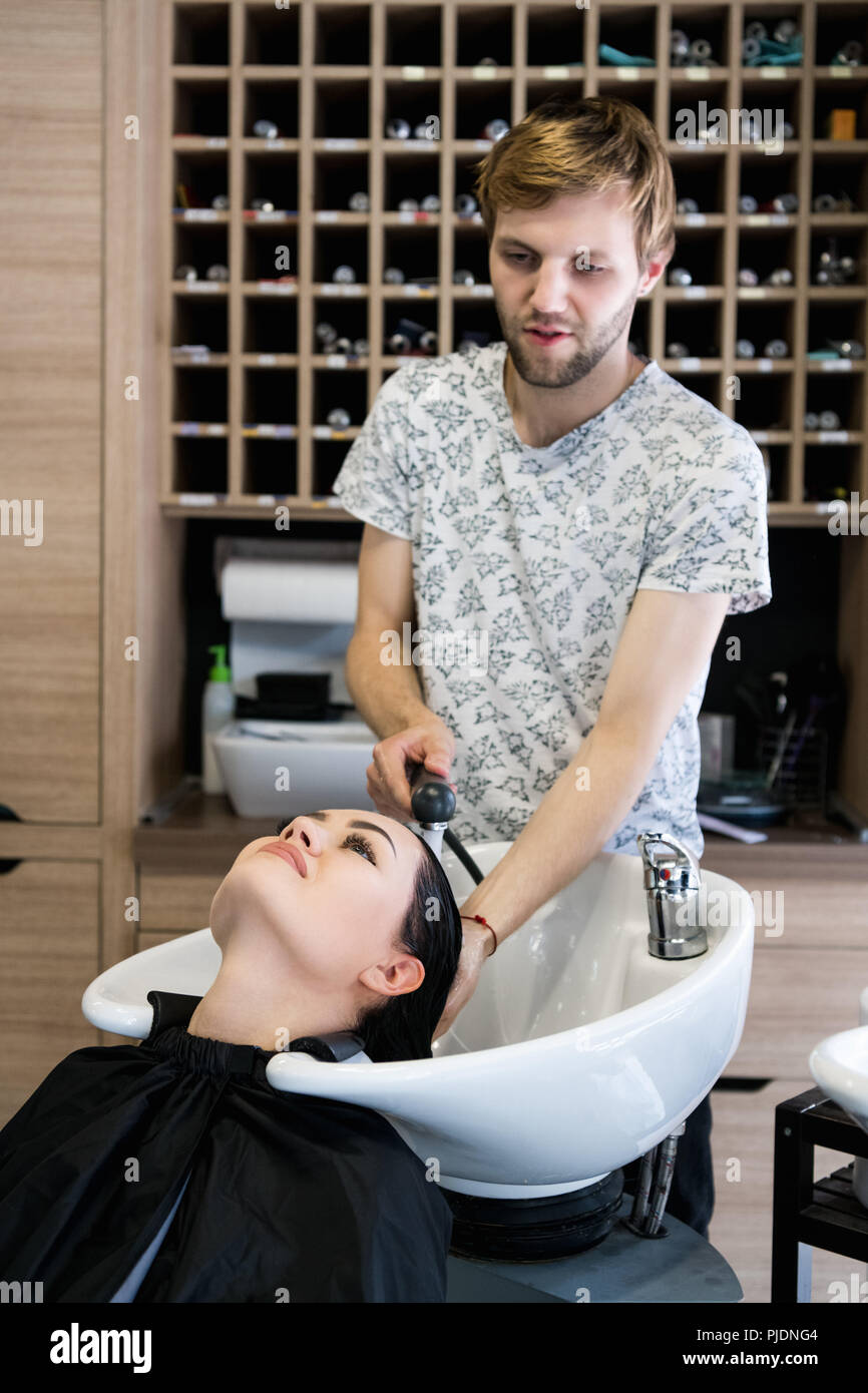 Coiffure homme lave-tête client. Un homme maître de cheveux cheveux de la fille d'un arrosage avec une douche dans un salon de coiffure. Photo Stock