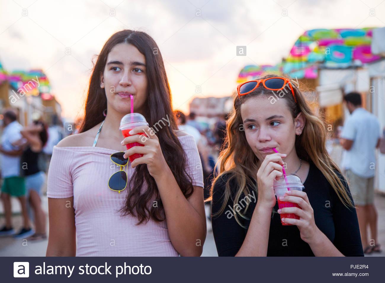 Deux adolescentes se promener dans un marché en plein air et prendre un bain rafraîchissant verre rouge. Photo Stock