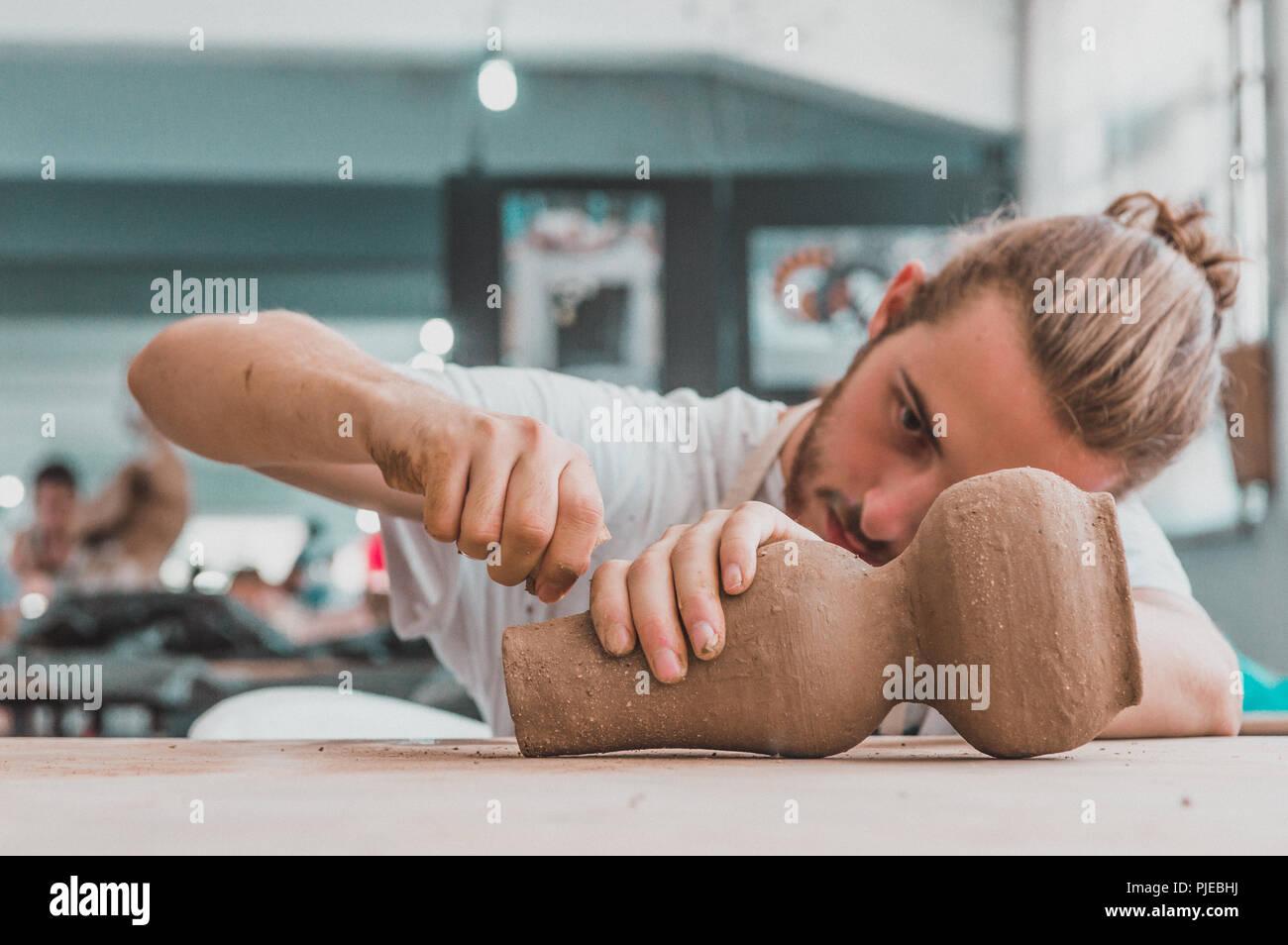 Jeune artiste poterie travaille sur son pot en argile dans un atelier Photo Stock