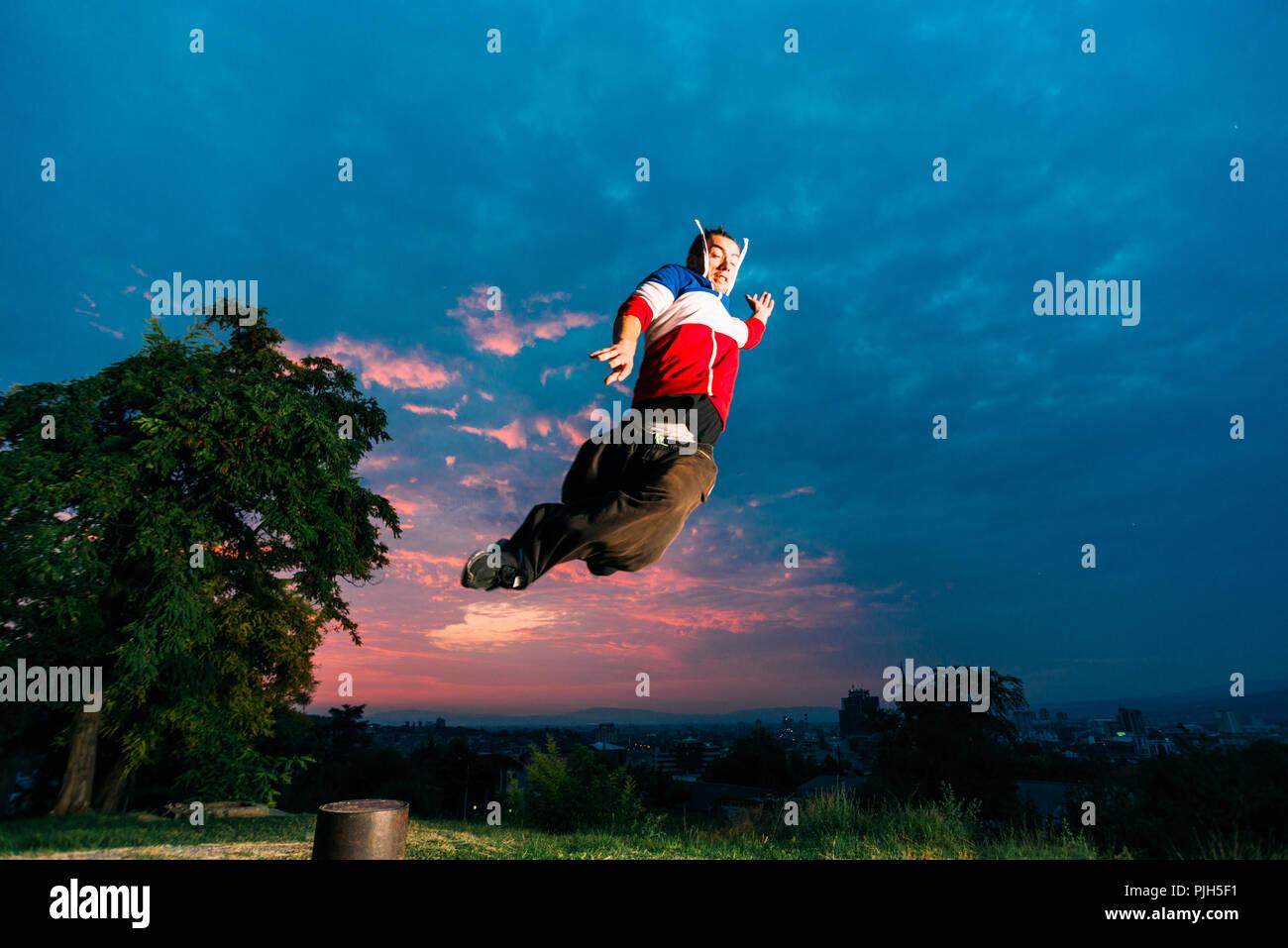 Jeune homme faisant parkour à soir Photo Stock