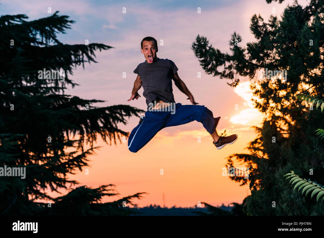 Homme libre exercice parkour runner en plein air lors d'un saut Photo Stock