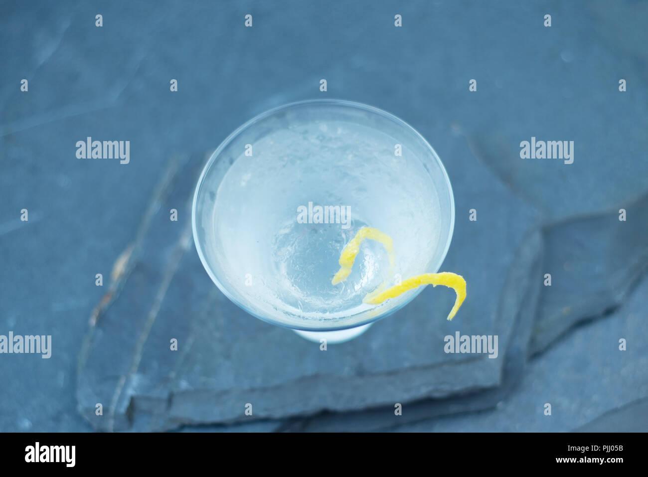 Sirotant une boisson vodka martini avec une torsion, secoué non remué, dans un verre à martini, au cours d'une arrière cour avec amis et famille. Photo Stock