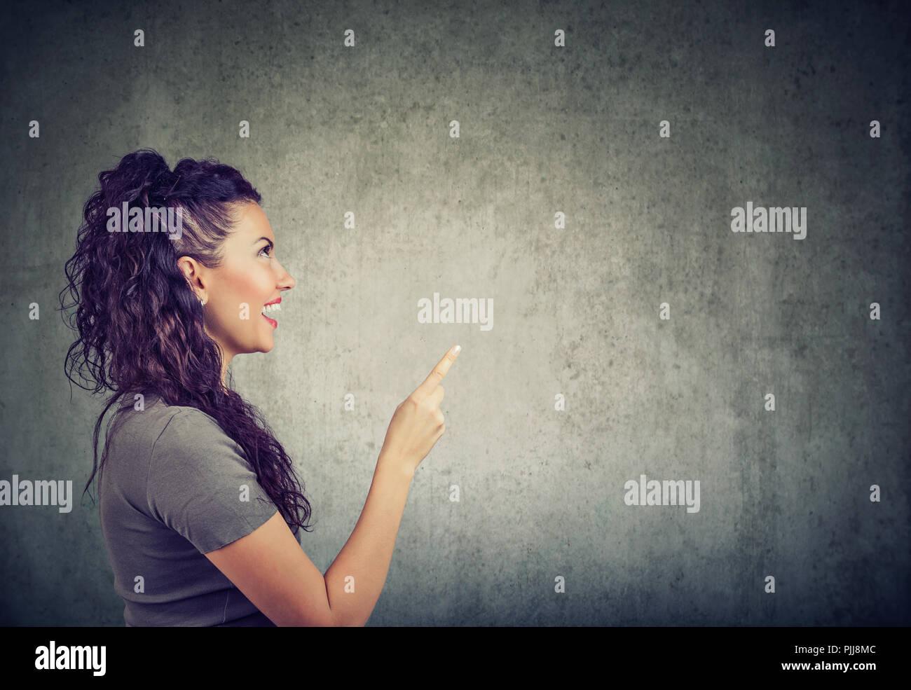 Vue latérale du doigt de maintien femme excitée par avoir idée lumineuse sur fond gris Photo Stock