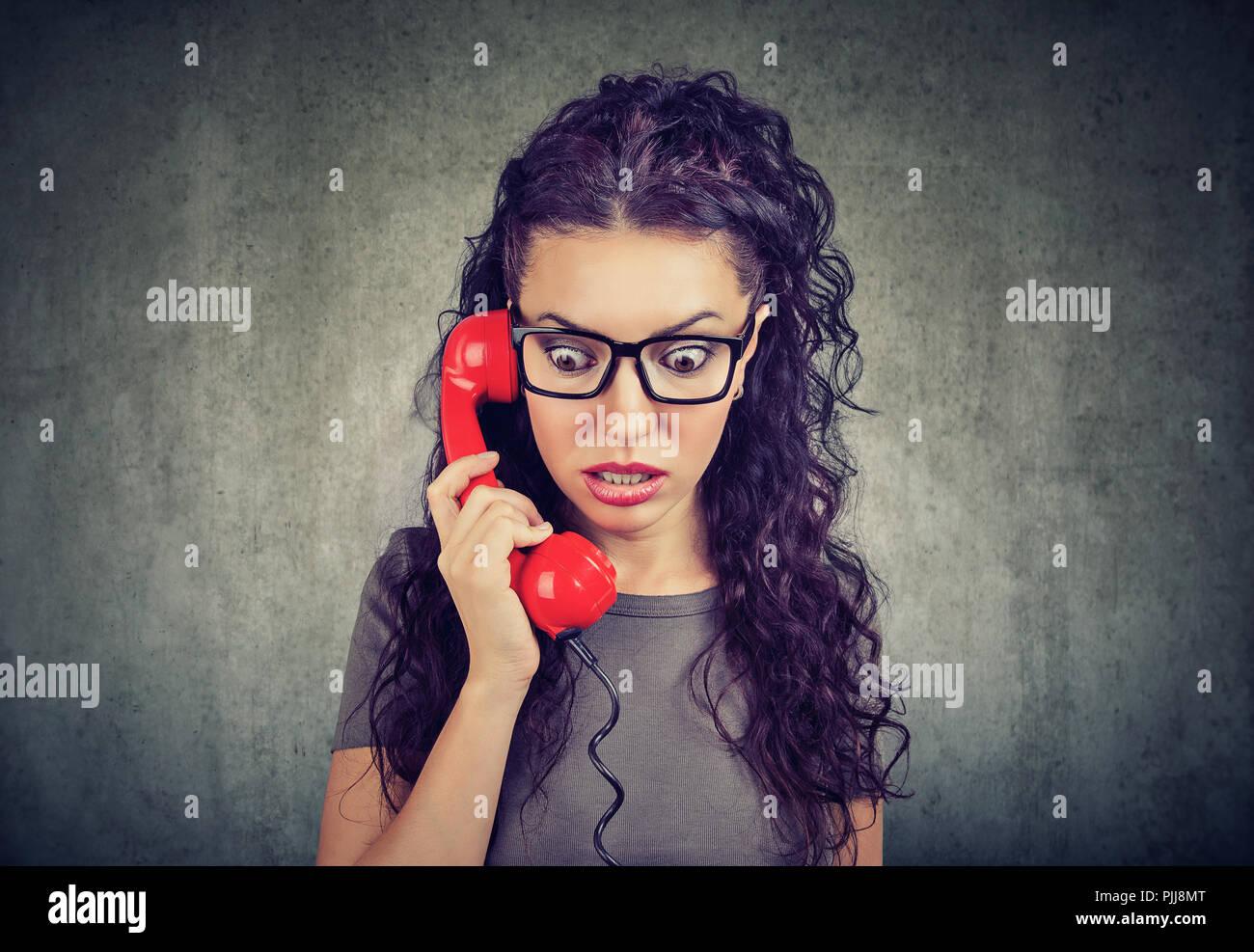 Woman receiving nouvelle choquante sur un téléphone et regardant vers le bas avec la peur. Photo Stock