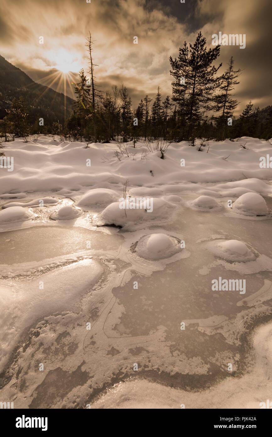 Coucher du soleil dans l'hiver, les zones humides de l'Isar, la glace et la neige Hill dans le lit, dans l'arrière-plan forest edge et le ciel du soir, or Banque D'Images