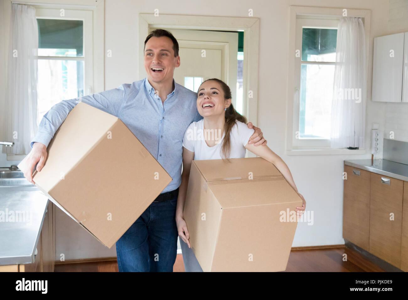 Heureux couple holding boxes moving dans de nouvelle maison Photo Stock