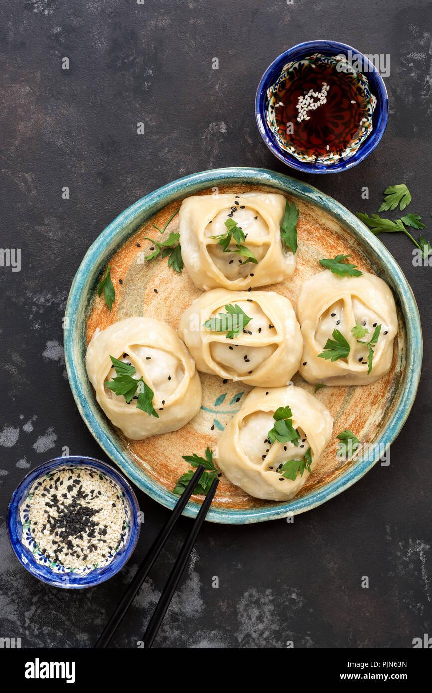 Asian dumplings à la vapeur, l'arrière-plan en béton noir, sauce soja, sésame. Vue de dessus , plat lay . La nourriture asiatique Photo Stock