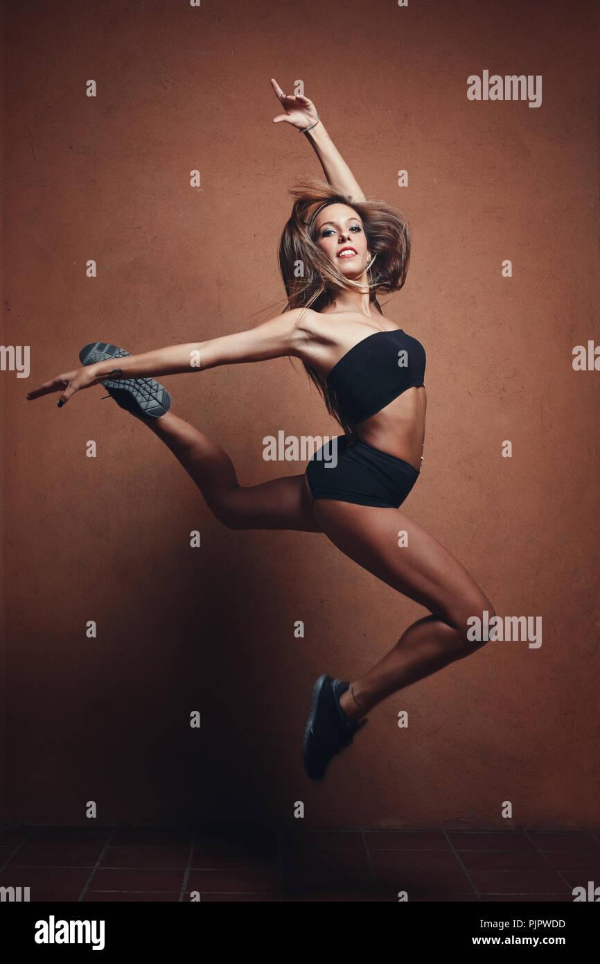 Belle gymnaste sauts. La danse moderne et de l'aérobique Banque D'Images