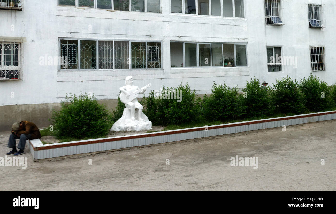 Le contraste d'un travailleur fatigué et las à la séance par statue blanche d'un heureux joueur de guitare, Kaesong, Corée du Nord Photo Stock