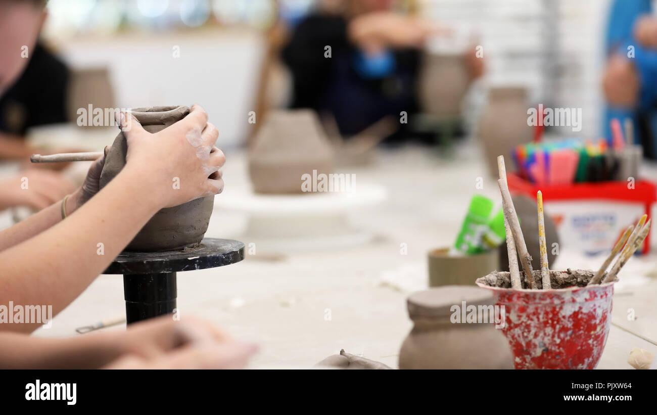 Les étudiants travaillant avec l'argile se salir les mains. La classe d'art visuel montrant les mains sur une bobine pot avec de l'argile tols et 24 en arrière-plan. Art professio Banque D'Images
