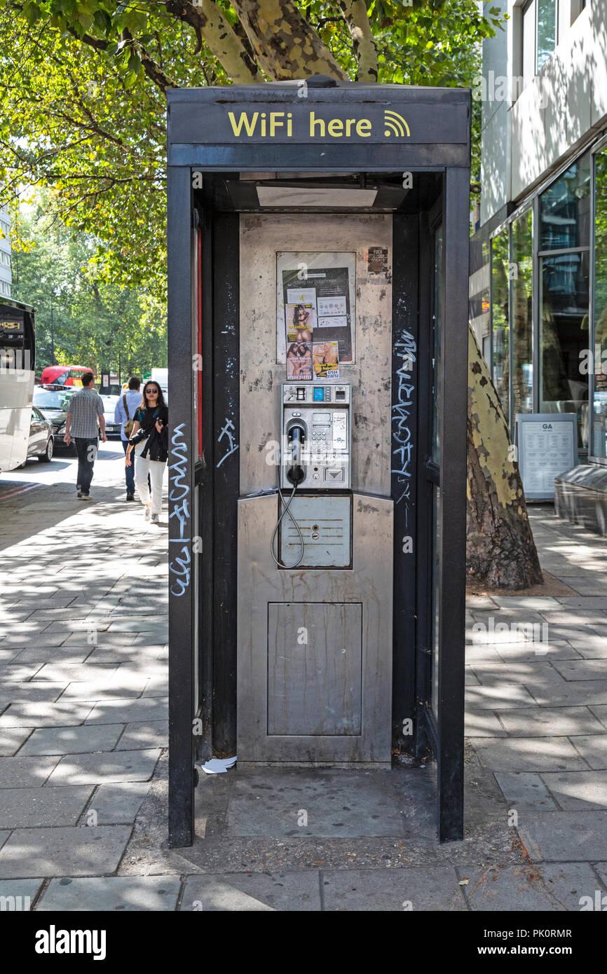 Une boîte de téléphone public vandalisé à Londres, Angleterre, publicité wi-fi, de graffiti et de services publicitaires cartes femme masseurs. Photo Stock