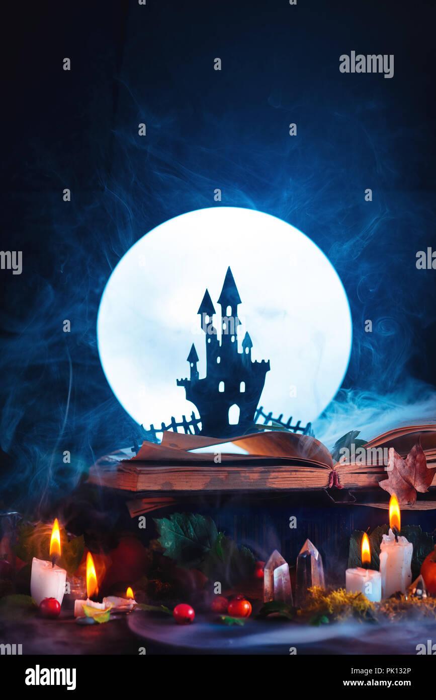 Concept d'Halloween avec un château hanté silhouette devant la pleine lune. Livre de sorts sur sorcière ou un assistant de travail. Toujours sur la vie magique de création Photo Stock