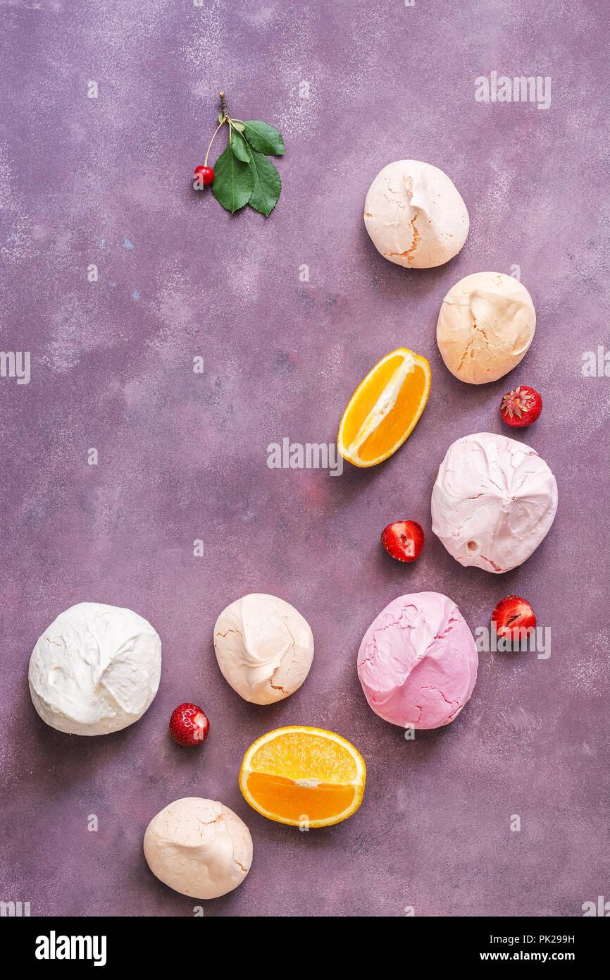 La meringue rose et beige est magnifiquement située sur un fond mauve avec des fraises, cerises et les tranches d'orange. L'espace de copie, vue du dessus Photo Stock