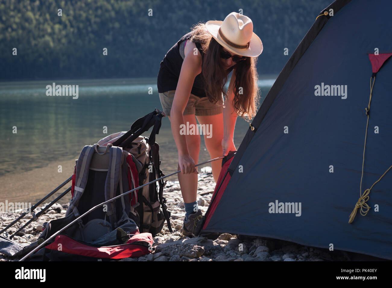 Femme setting up tent Banque D'Images