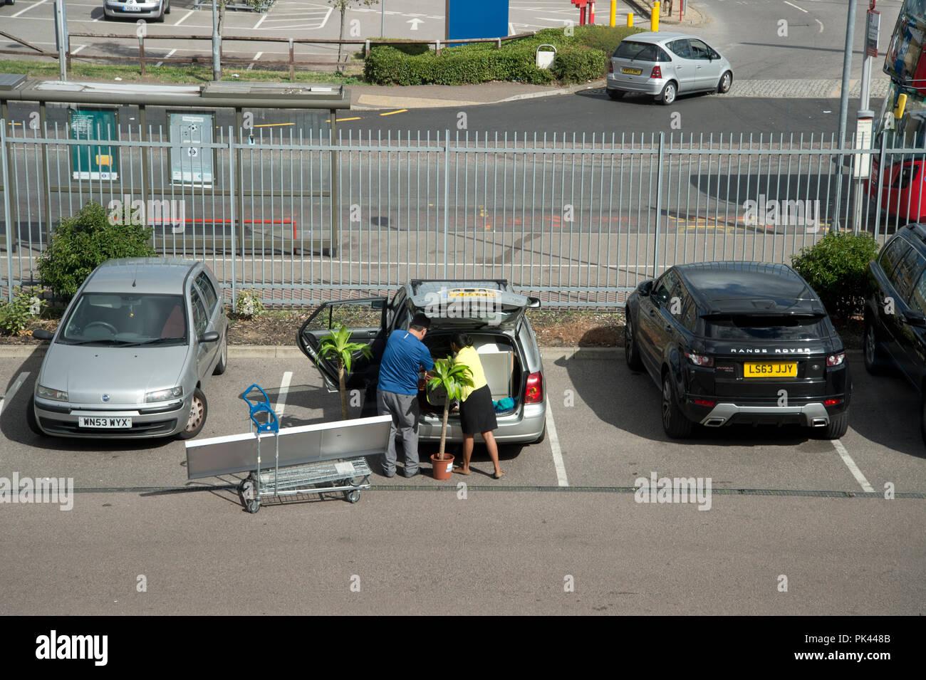 Ikea , Edmonton, au nord de Londres. Couple d'essayer de mettre en place les achats dans le coffre d'une voiture. Photo Stock