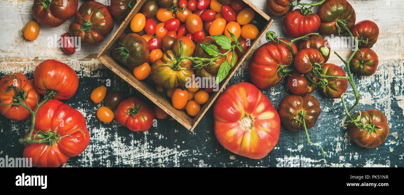 Télévision à jeter de produits frais mûrs colorés de l'automne ou l'été heirloom, bunch et tomates cerises sur fond de bois rustique, vue du dessus, composition horizontale. Lo Photo Stock
