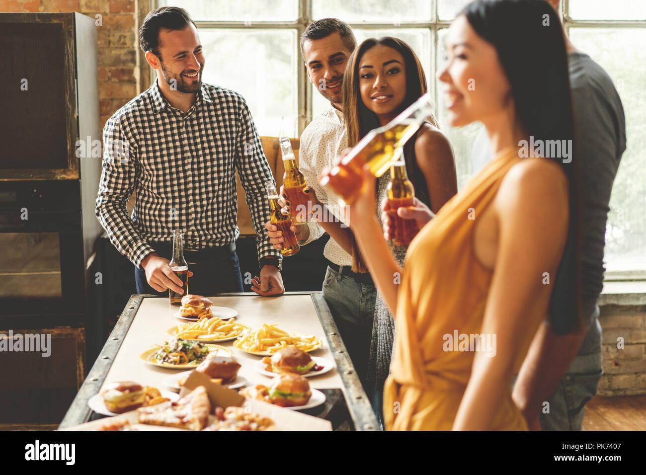 Home party. Toute la longueur de cheerful young people enjoying home party lors de la communication et de manger des collations sur la cuisine. Photo Stock