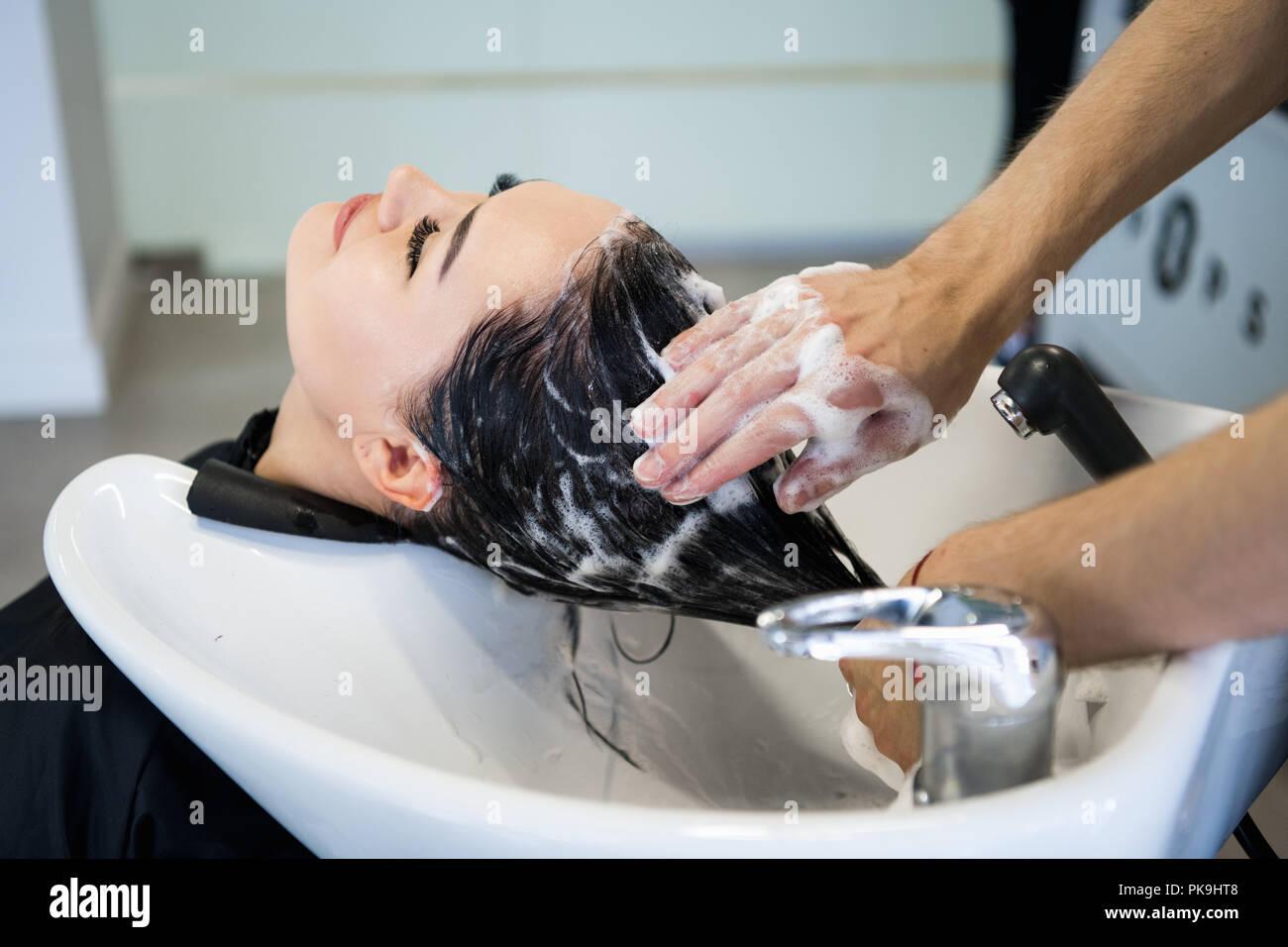 Méconnaissable coiffeur professionnel lavage des cheveux de son client. Belle coiffure laver les cheveux de sa cliente dame en coiffure. Séance du client avec les yeux fermés. Photo Stock